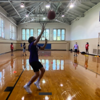 A girl gets a rebound in an instructional basketball class.