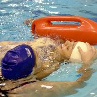 Two students perform an exercise in a lifeguard training class.