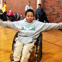 A wheelchair basketball player smiles big.