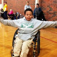 A boy in a wheelchair smiles for a photo in the middle of a special recreation program.