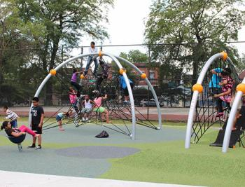 A number of kids explore the brightly colored and super fun playground equipment at Cornell Square Park.