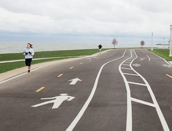 A woman runs along the Lakefront trail running path.