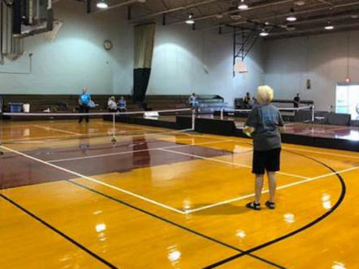A group enjoys a game of pickleball at one of the Chicago Park District's indoor pickleball courts.