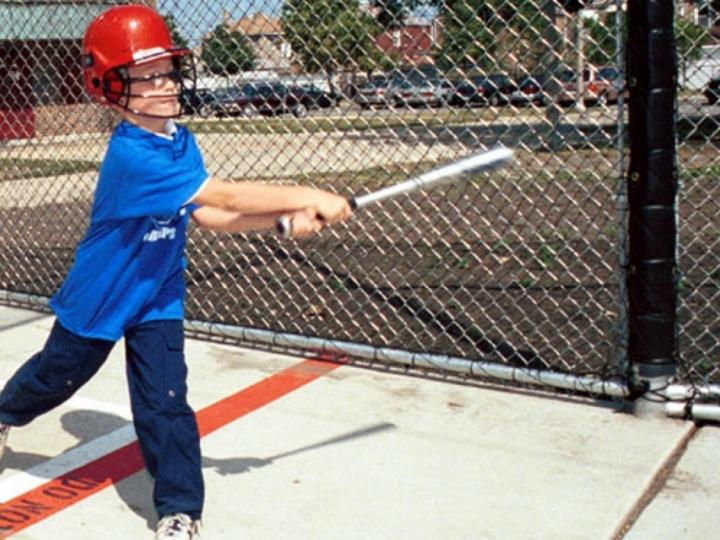 Kid taking a swing at the batting cages.