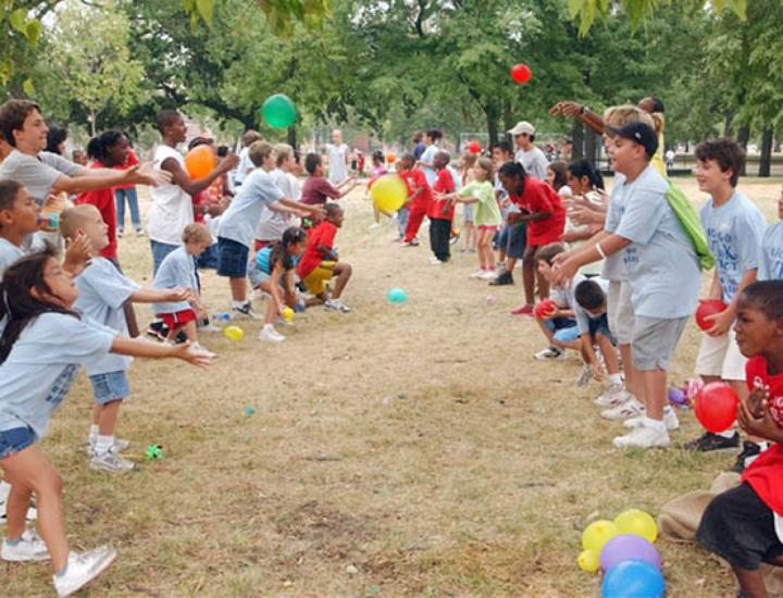 Kids enjoy a game of balloon toss outside during a fun day of summer camp.