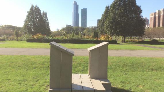 Double sided podium sitting on grass against high rise buildings in downtown Chicago.