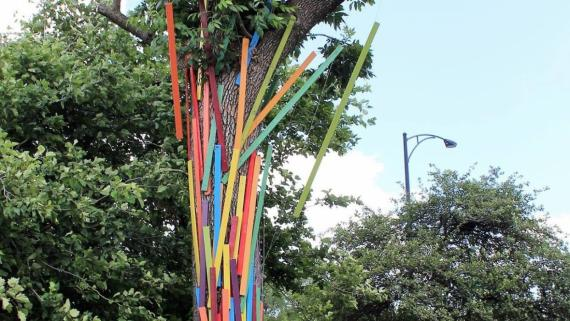 Artist Gary Lehman standing in front a tree decorated with colorful painted wood pieces.