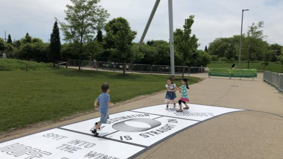Young kids on an over-sized black and white hopscotch with inspirational messages printed on the squares.