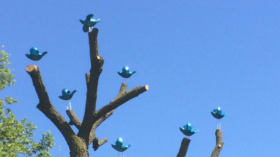 Blue carved wood birds perched in a tree.