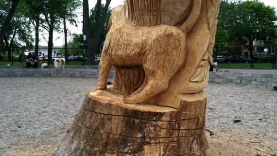 Dogs in relief sculpted into the base of a tree shaft.