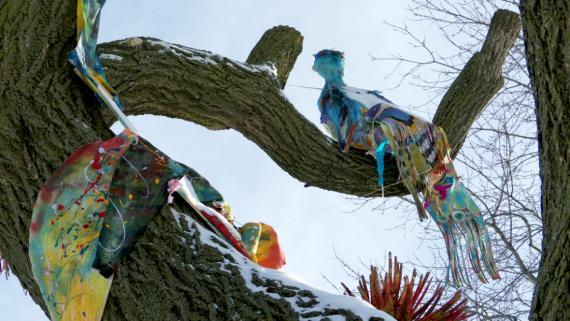 Brightly colored birds made form recycled materials are perched on the branches of a dead tree.