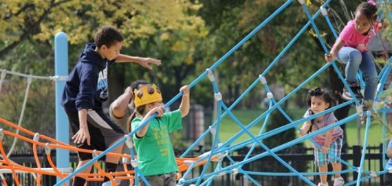 Kids climbing the new playground equipment at Riis Park.