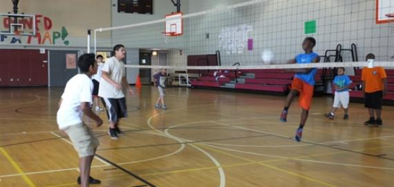 Participants having fun playing volleyball with recreation leaders