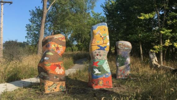 Three colorfully tiled towers sitting in a grassy area.
