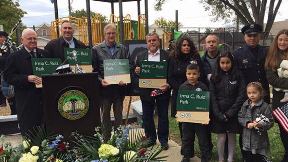 General Superintendent & CEO Michael Kelly, Alderman Ed Burke and the family of Irma C. Ruiz stand for a photo, each with a Irma C. Ruiz park sign, at the renaming event.